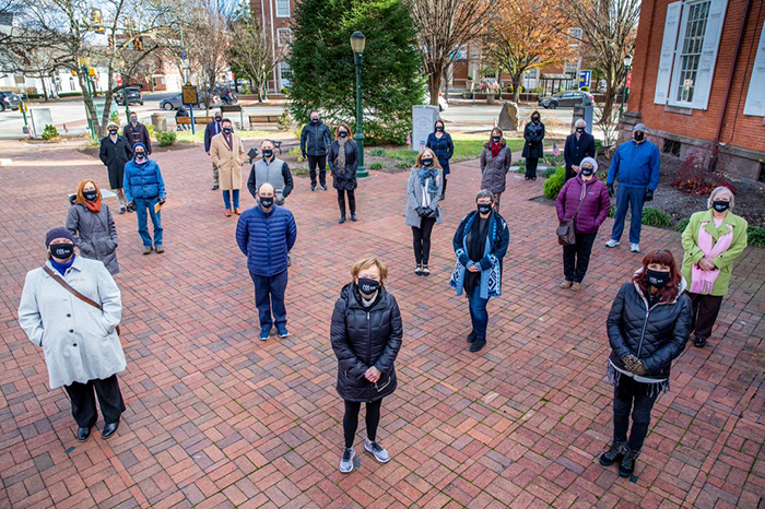 "Members of Carlisle's Community Action Network pose in the town square. ""If we all do our part, we'll be able to stem the spread,"" said President Margee Ensign (front row, second from left)."