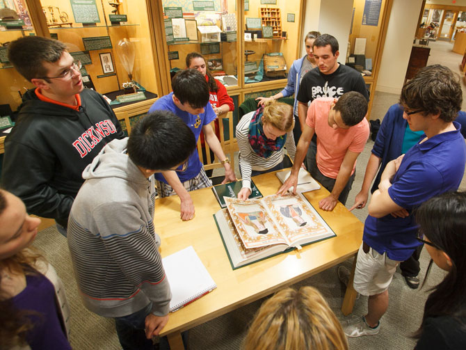 Students looking at a manuscript in the Dickinson archives.