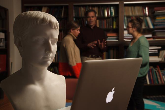 A classic bust looking at a computer screen in the foreground while a professor and two students talk in the background.