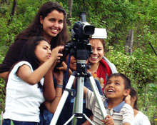 A Dickinson student helps some children with a video camera.