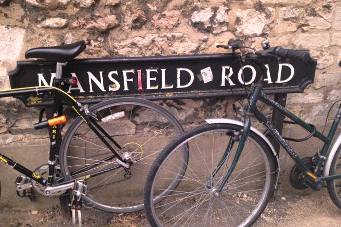 Bicycles rest against a Mansfield Road sign.