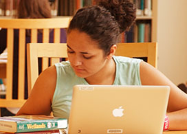 A female student sitting at a table in the library while working on her computer.