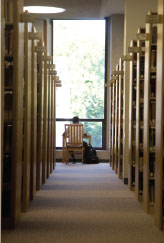 student sitting at table at far end of aisle between rows of bookshelves in the library