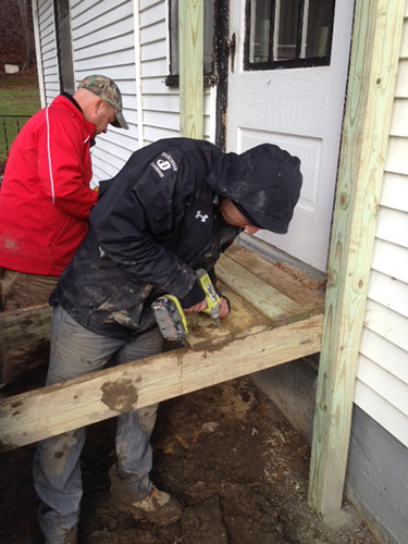 a student on the lacrosse team joins Head Coach Dave Webster on a building project in West Virginia.